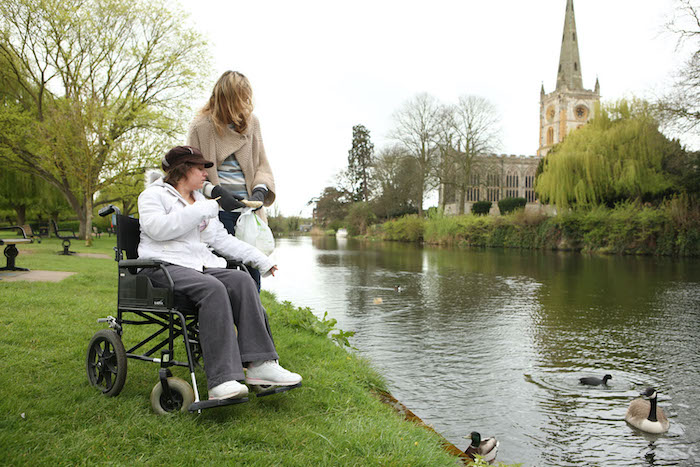 Helping Hands live-in carer feeding ducks with a customer